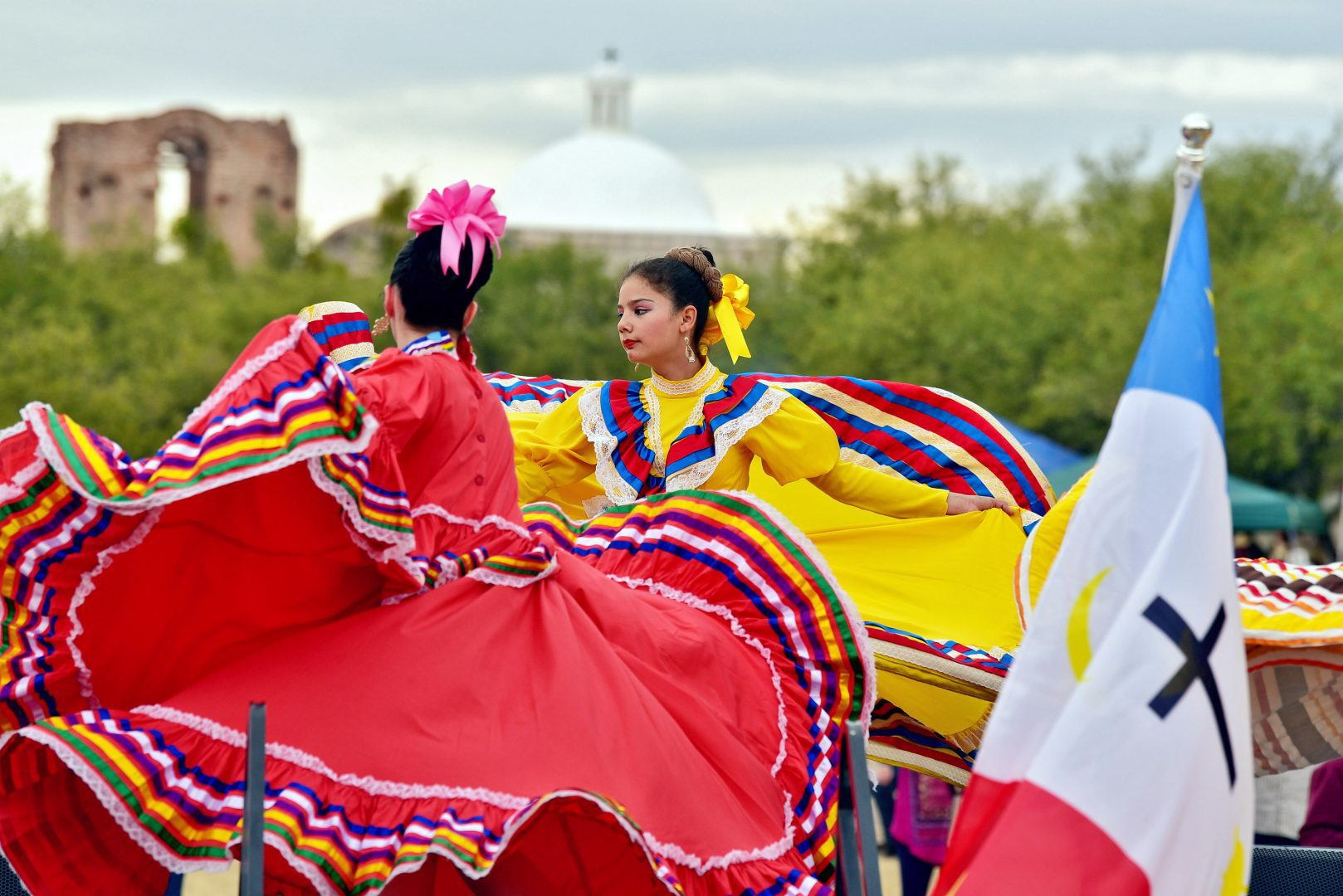 Hispanic dancers in colorful dresses in from of Tumacácori mission